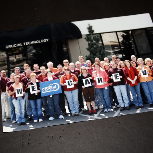 "Photograph from employees of Crucial Technology with placards stating ""We -Crucial- Care VT"""
