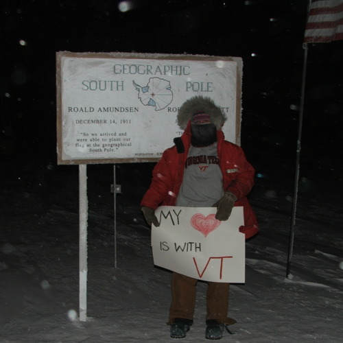 "Kari, a female worker, with Virginia Tech attire, standing in front of the Amundsen-Scott South Pole Station sign, holding a poster that says, ""My [heart] is with VT."""