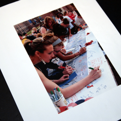 Photograph of Western Connecticut State University students signing a banner to send to Virginia Tech